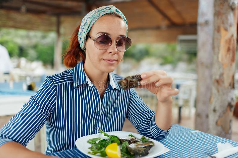 Young woman eating oyster in an outdoor restaurant stock images