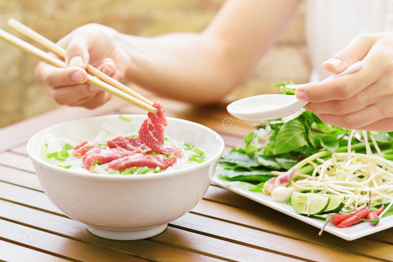 Young woman eating the Pho Bo in street cafe of Vietnam royalty free stock photo