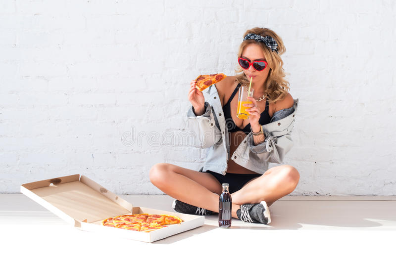 Young woman eating a piece of pizza drinking juice sitting on floor wearing sunglasses stock photo