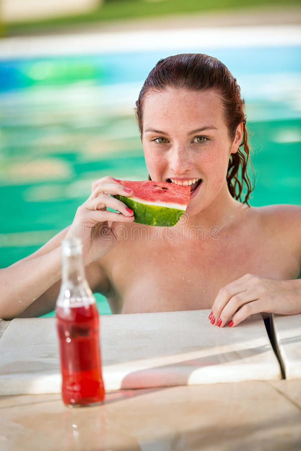 Young woman eating piece of watermelon in pool stock images