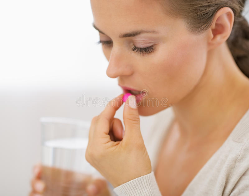 Young woman eating pill. Young woman in living room eating pill stock photo