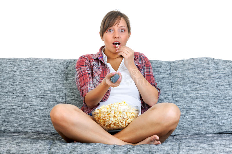 Young woman eating popcorn. While watching tv isolated on white background stock photo