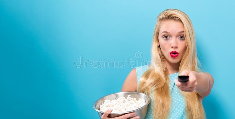 Young woman eating popcorn stock images