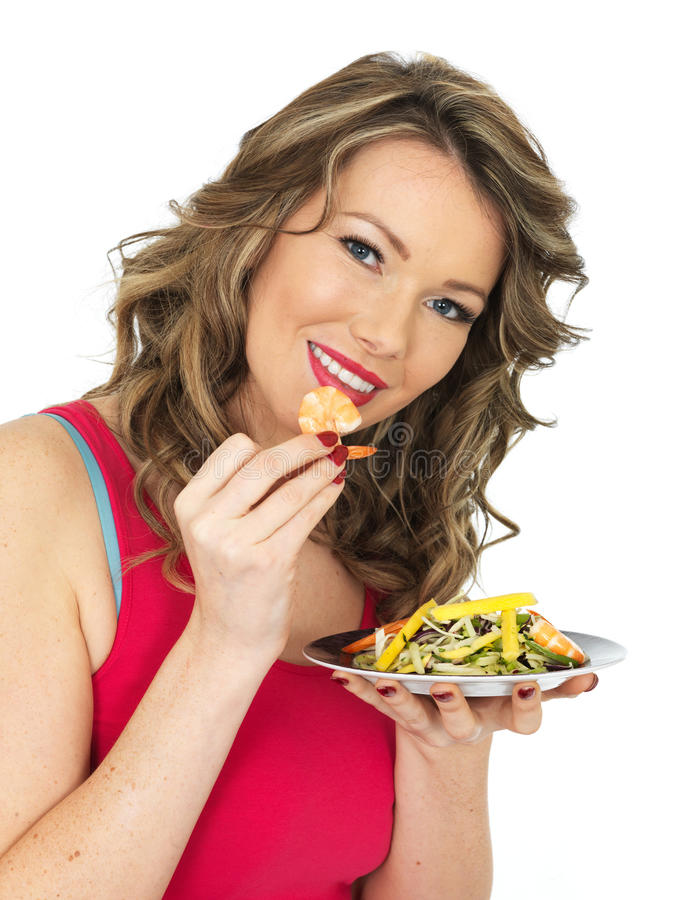 Young Woman Eating a Prawn and Mango Salad royalty free stock photos