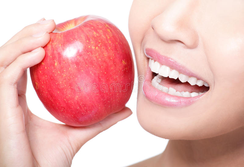 Young woman eating red apple with health teeth. Beautiful young woman eating red apple with health teeth. Isolated over white background, asian beauty model royalty free stock photo
