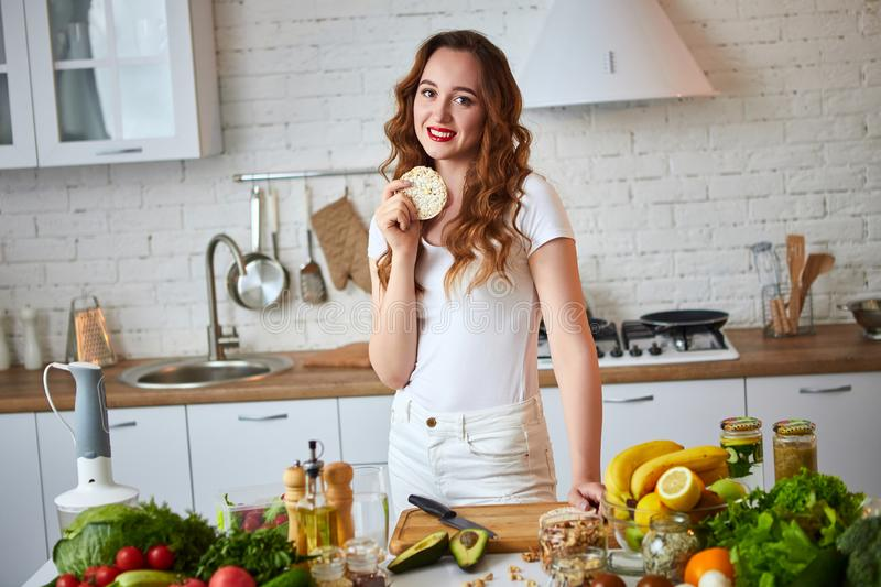 Young woman eating rye cracker crisp bread in the kitchen. Healthy Lifestyle. Health, Beauty, Diet Concept. Young woman eating rye cracker crisp bread in the stock image
