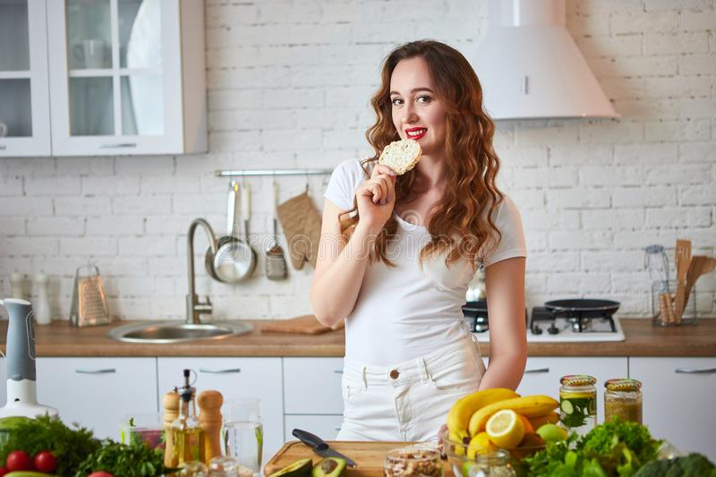 Young woman eating rye cracker crisp bread in the kitchen. Healthy Lifestyle. Health, Beauty, Diet Concept. Young woman eating rye cracker crisp bread in the royalty free stock photos