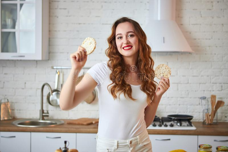 Young woman eating rye cracker crisp bread in the kitchen. Healthy Lifestyle. Health, Beauty, Diet Concept. Young woman eating rye cracker crisp bread in the stock images