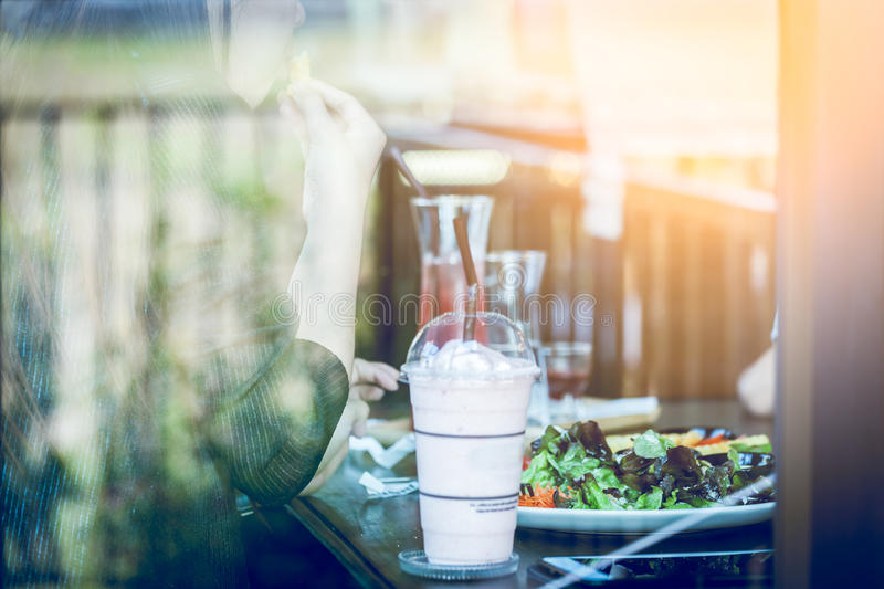 Young woman eating salad and beverage in cafe. Focus woman stock photos