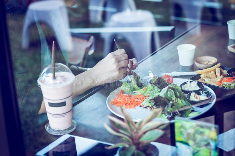 Young woman eating salad and beverage in cafe royalty free stock photo