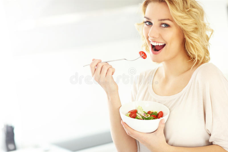 Young woman eating salad in the kitchen. A picture of a young woman eating salad in the kitchen royalty free stock photography