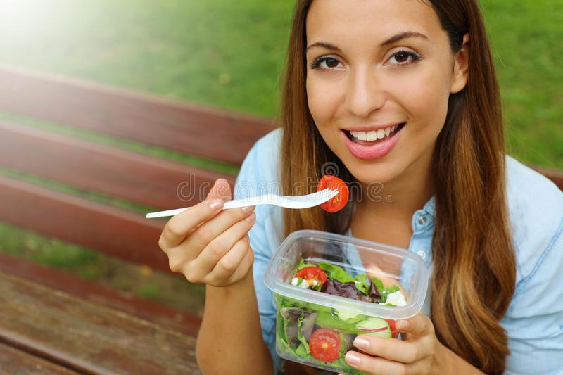 Young woman eating salad on lunch break in city park living healthy lifestyle. Happy smiling brazilian girl eating outdoor royalty free stock photography