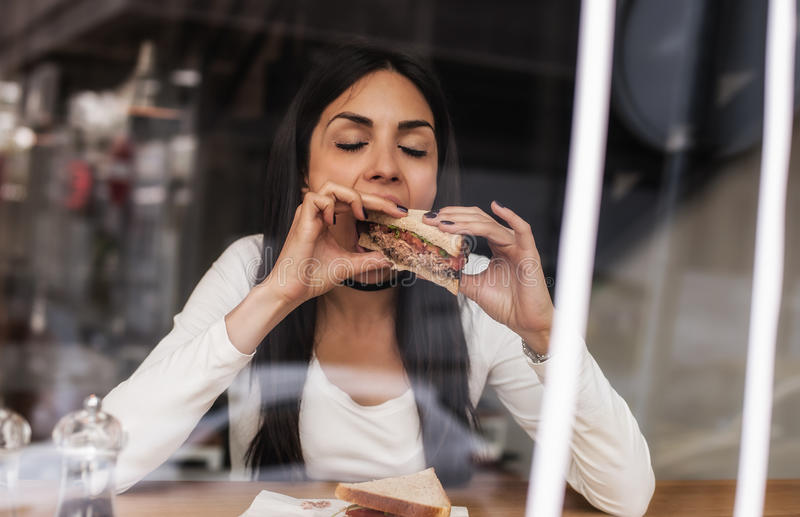 Young woman eating a sandwich in fast food cafe. Cafe window. Portrait of young woman eating a sandwich in fast food cafe. Cafe window stock photography