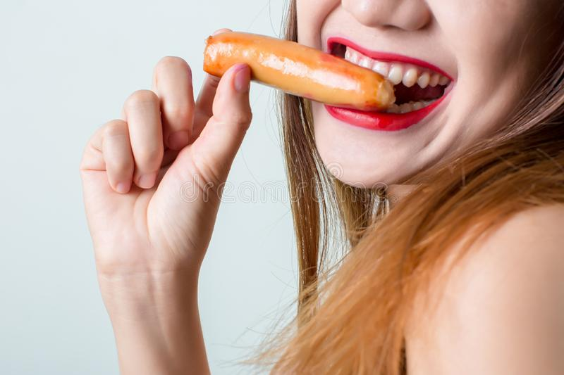 Young woman eating sausage or hotdog. girl is sitting in the kitchen and greedily eats sausage. stock image