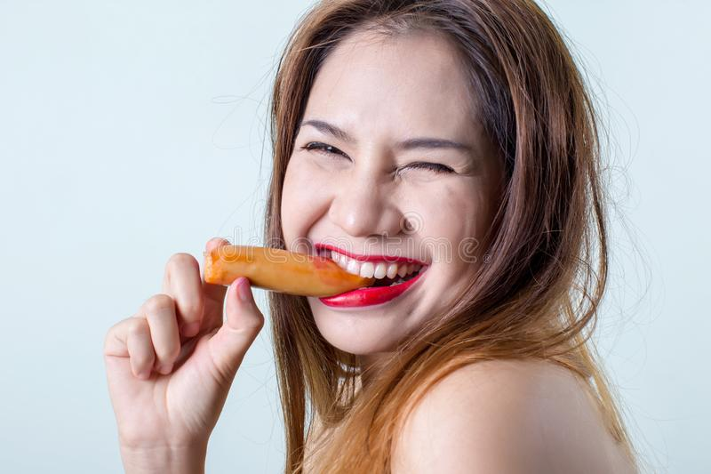 Young woman eating sausage or hotdog. girl is sitting in the kitchen and greedily eats sausage. royalty free stock photo