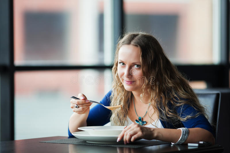 Young fashion woman eating soup at restaurant royalty free stock image