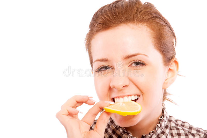 Young woman eating sour lemon, making grimace stock image