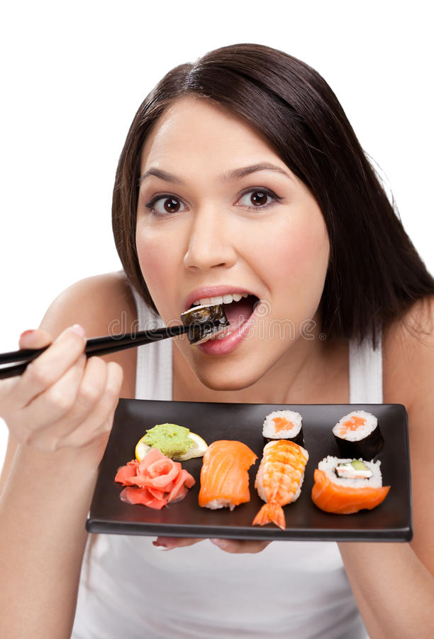 Young woman eating sushi. Young attractive woman eating sushi with a chopsticks, isolated royalty free stock photography