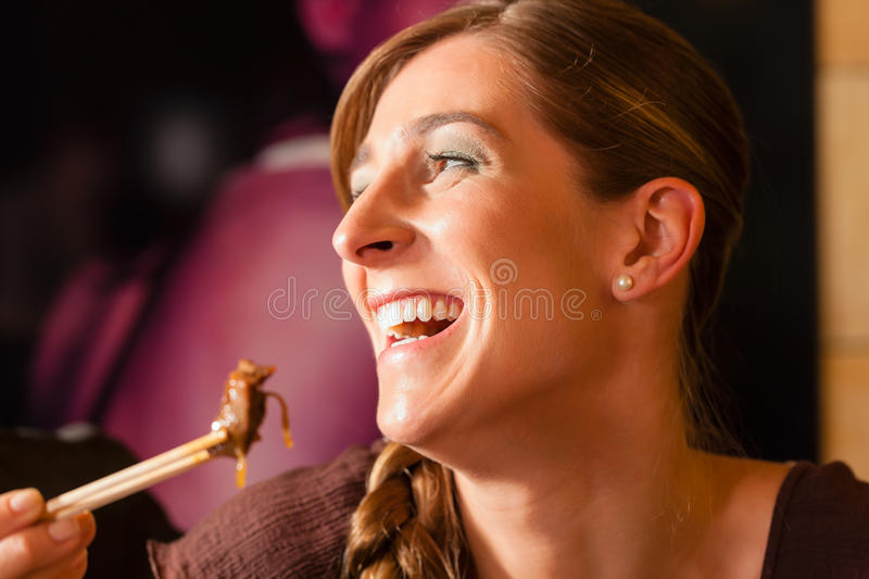 Young woman eating in Thai restaurant. Young woman eating in a Thai restaurant, she is eating with chopsticks stock images