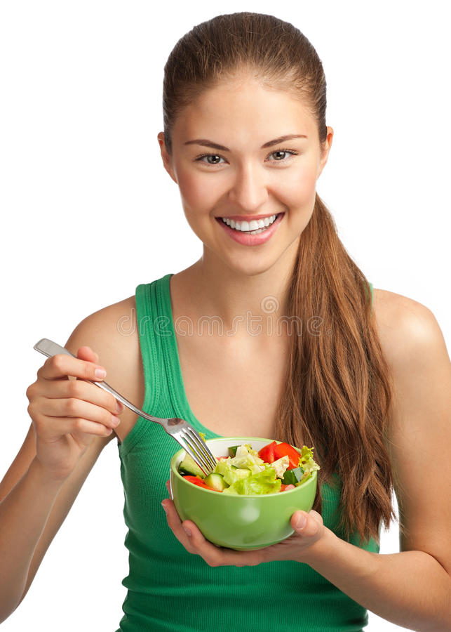 Young woman eating vegetable salad. Portrait of a pretty young woman eating vegetable salad against white background royalty free stock images