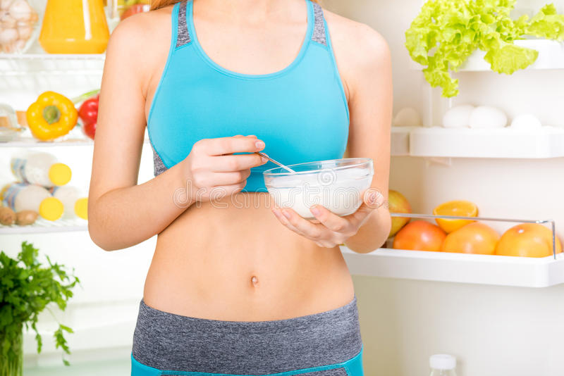 Young woman eating a yogurt and staying near the fridge full of health food. Fitness and healthy lifestyle concept royalty free stock image