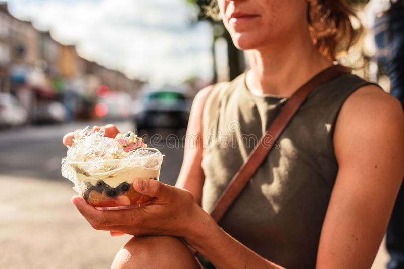 Young woman eating yogurt in the street stock photo