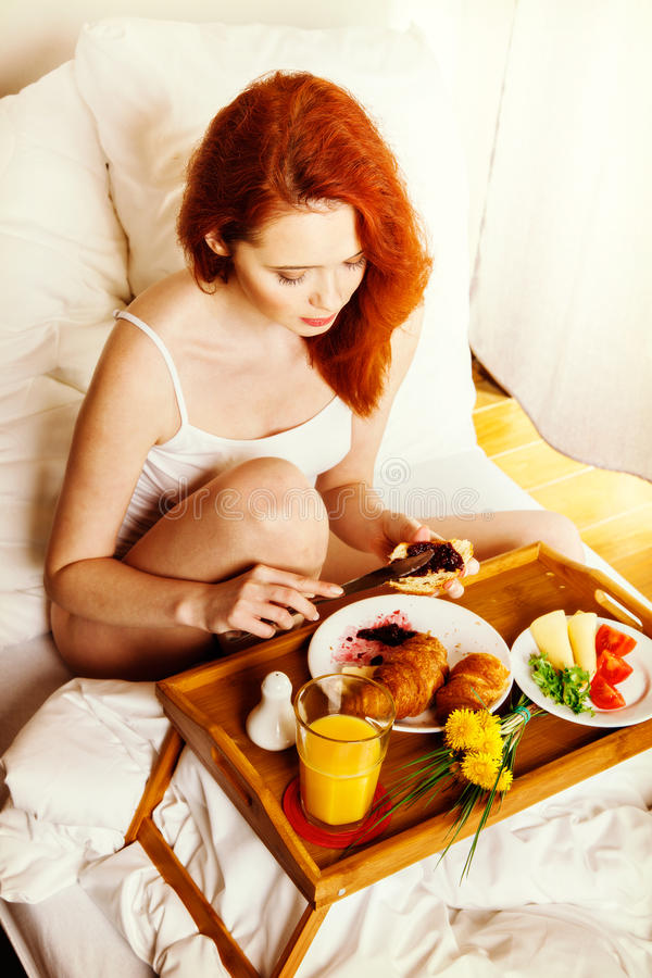 Young woman eats breakfast in bed in the morning. Lifestyle concept. Toned image stock photo