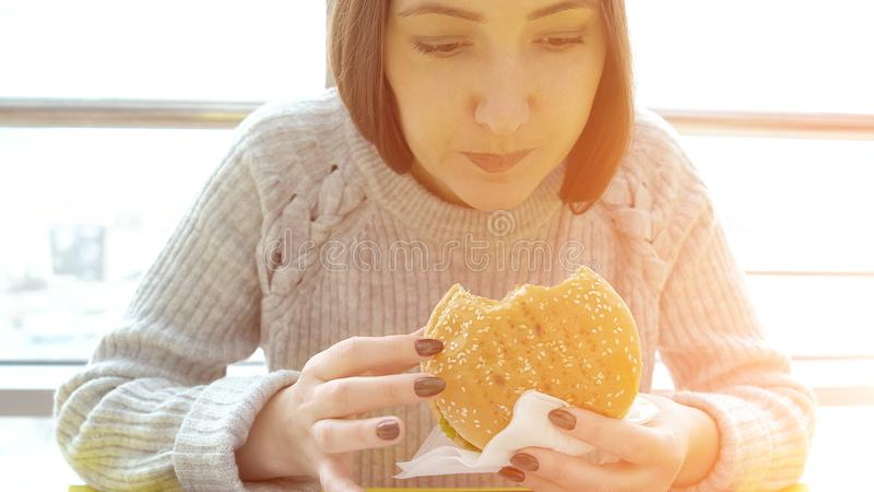 Young woman eats a burger. Harmful fatty foods stock image