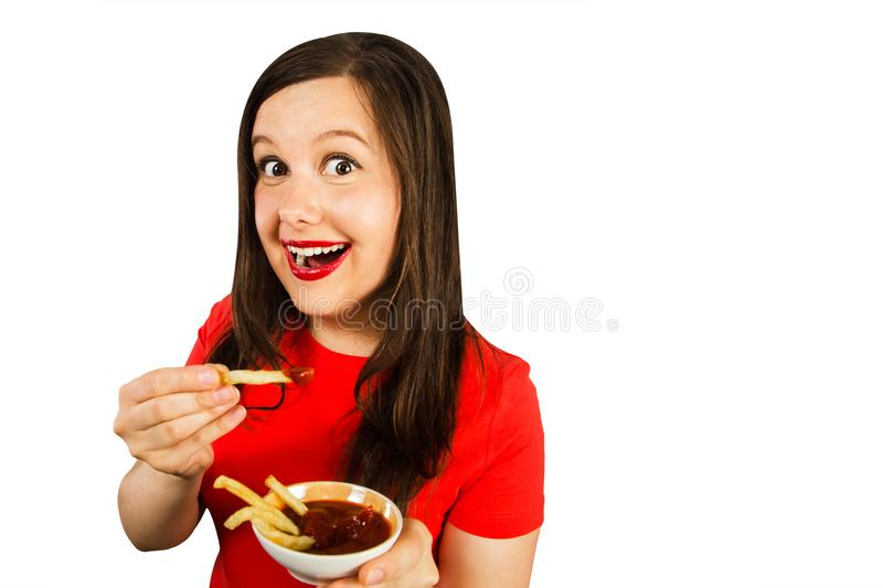 Young woman eats fries with ketchup. Isolated on white background stock image