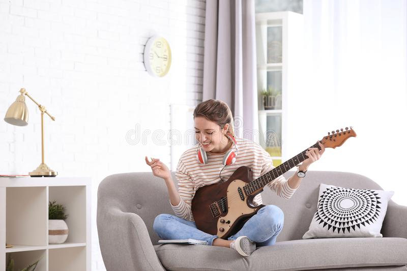 Young woman with electric guitar composing song stock photos