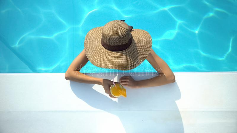 Young woman in elegant hat swimming in pool and enjoying delicious cocktail royalty free stock image