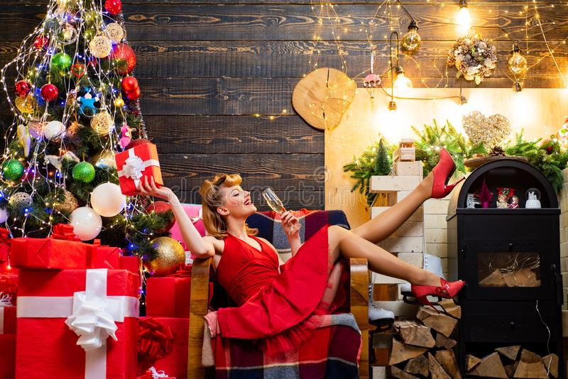 Young woman in elegant red dress over Christmas interior background. Pretty girl wearing in red Christmas dress. royalty free stock photo