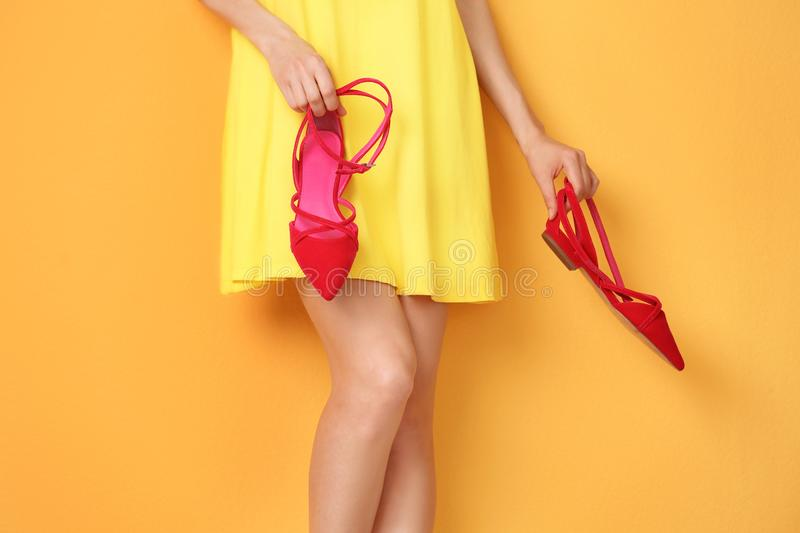 Young woman with elegant shoes on color background stock images