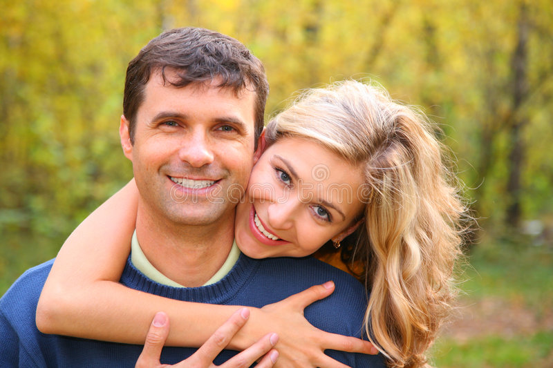 Young woman embraces man from back in autumn stock photography