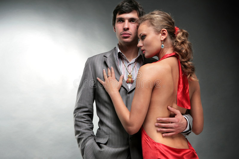 Young woman embraces man. Woman in a red dress. Man has turned away from the girl. The girl holds the guy for a collar of a jacket. Woman looks at the man royalty free stock photos