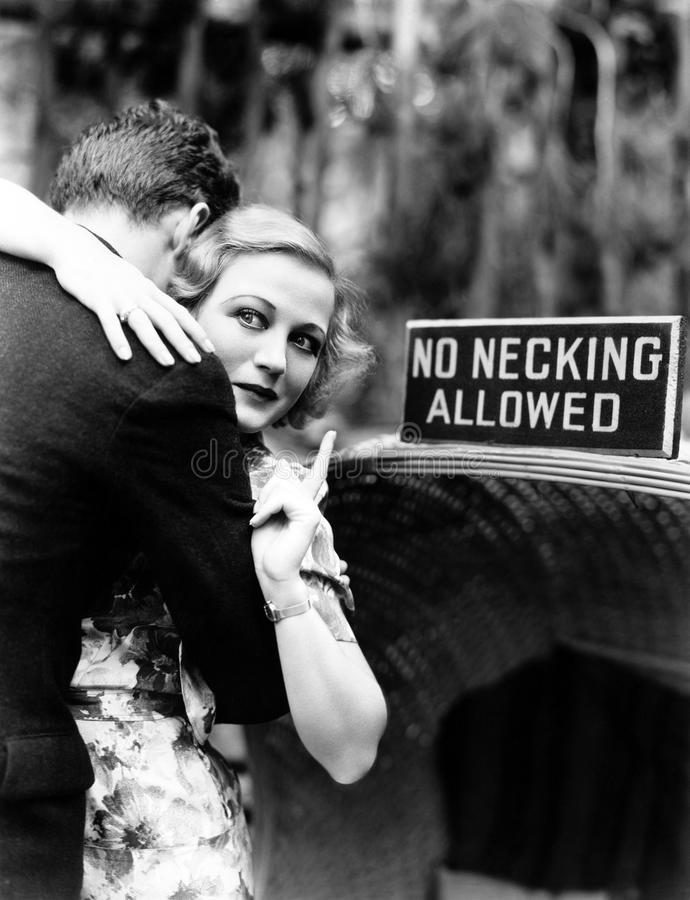 Young woman embracing a man and pointing towards an information board stock image