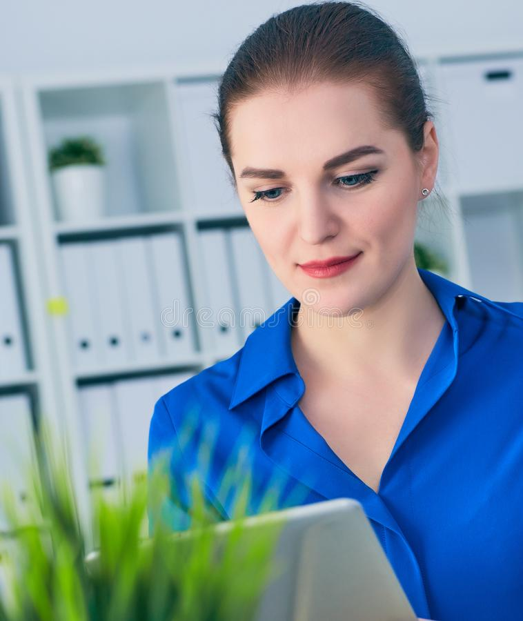 Young woman employee watching video or reading newspaper on digital tablet while sitting in modern office interior. Young woman employee watching video or stock photography