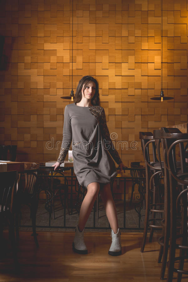 Young woman in empty restaurant. Young woman in trendy dresses waiting in the modern restaurant, caffee royalty free stock images