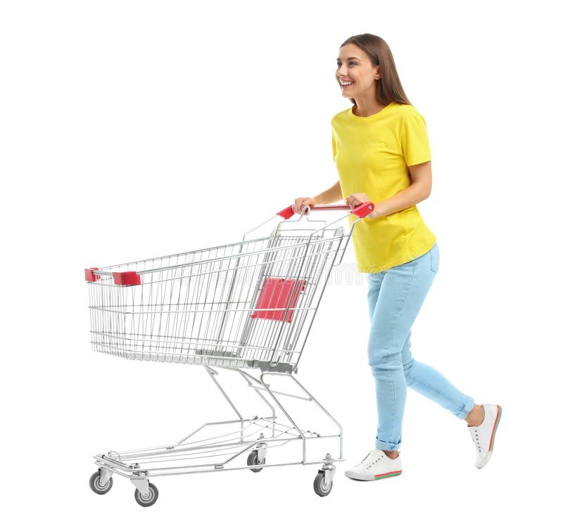 Young woman with empty shopping cart on background. Young woman with empty shopping cart on white background royalty free stock photo