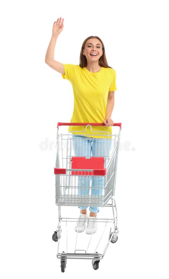 Young woman with empty shopping cart on background. Young woman with empty shopping cart on white background stock photography