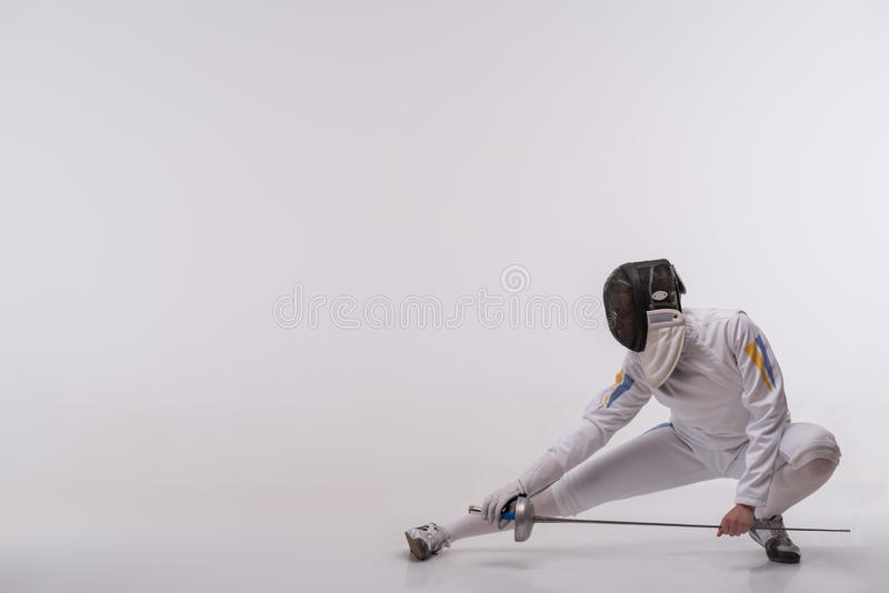 Young woman engaging in fencing. Full-length portrait of woman wearing white fencing costume and black fencing mask sitting like ninja looking at us. Isolated on stock photos