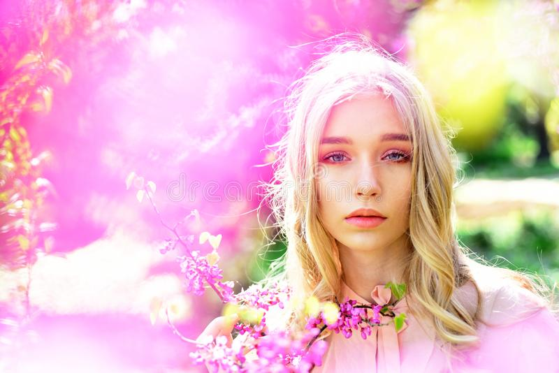 Young woman enjoy flowers in garden, defocused, close up. Lady in park on spring day. Spring bloom concept. Girl on. Dreamy face, tender blonde near violet stock photos