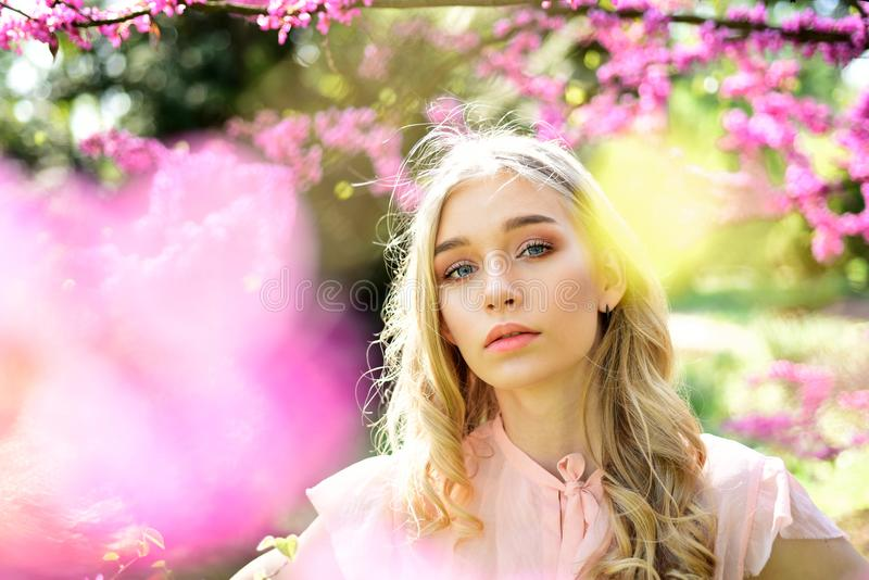 Young woman enjoy flowers in garden, defocused, close up. Spring bloom concept. Lady in park on spring day. Girl on. Dreamy face, tender blonde near violet stock image
