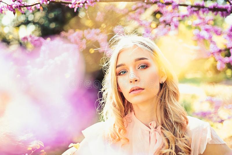 Young woman enjoy flowers in garden, defocused, close up. Spring bloom concept. Lady in park on spring day. Girl on. Dreamy face, tender blonde near violet royalty free stock images