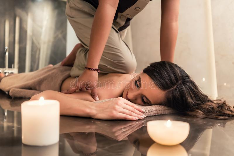 Young woman enjoying the acupressure techniques of Thai massage. Young women lying down while enjoying the acupressure techniques of traditional Thai massage at royalty free stock photos