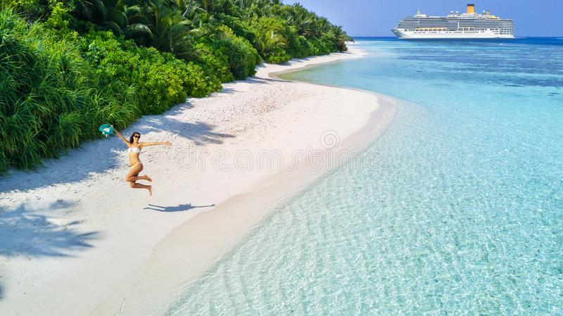 Young woman enjoying beach and cruise holidays. Happy young woman with luxury cruise boat on background. Tropical island on background. Concept of long-distance royalty free stock photo