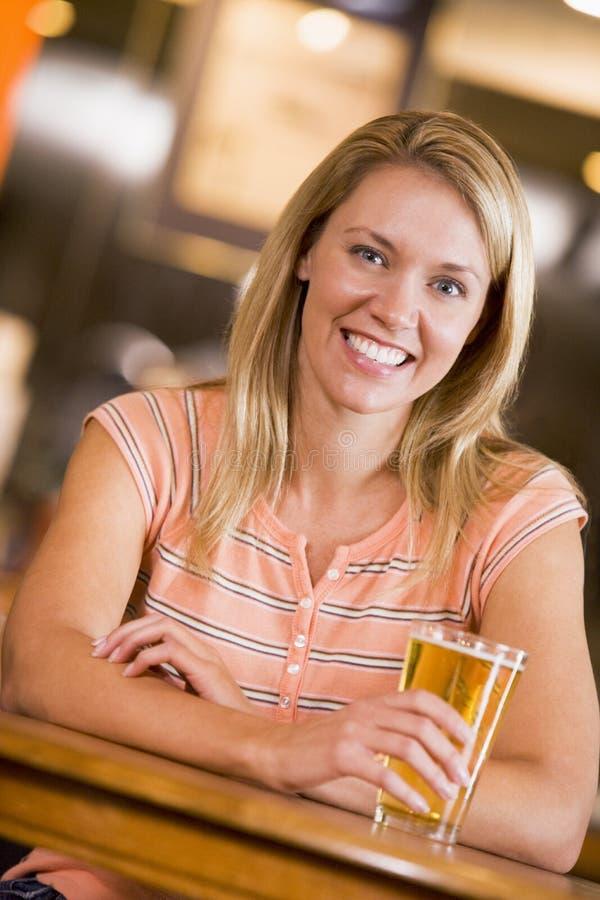 Young woman enjoying a beer at a bar stock photo