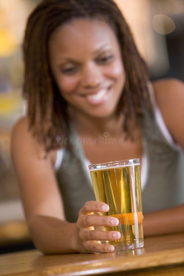 Young woman enjoying a beer at a bar stock images