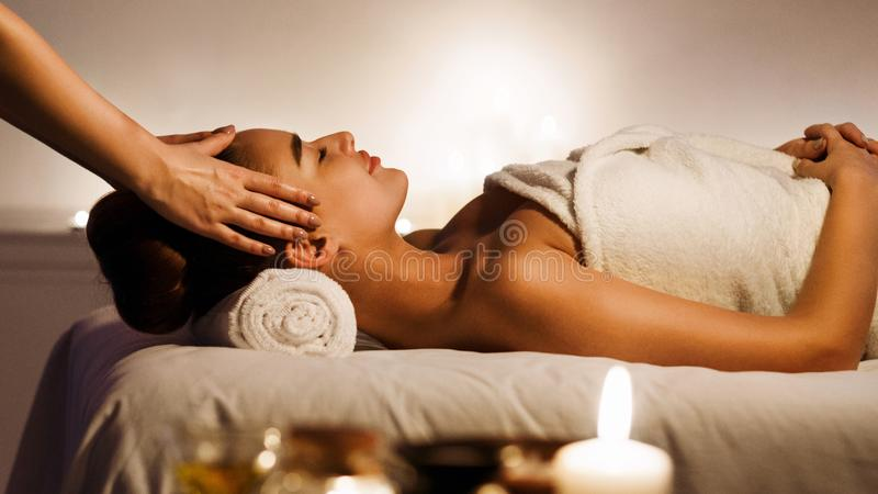 Young woman enjoying face massage in spa salon stock images