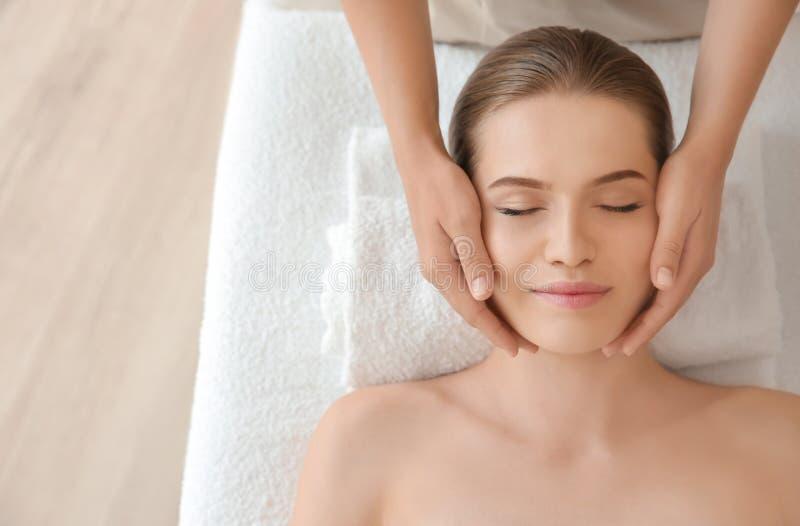 Young woman enjoying of facial massage royalty free stock photography